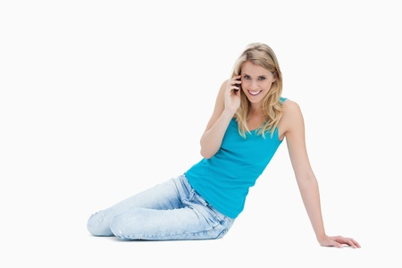 answering call: A smiling woman is sitting on the floor talking on her mobile phone against a white background