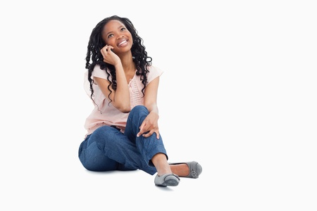 A smiling woman sitting on the floor is talking on her mobile phone and looking up against a white background Stock Photo - 13674736