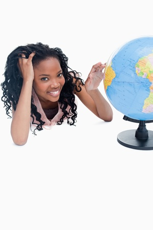 A young smiling girl has her hand on a globe against a white background photo
