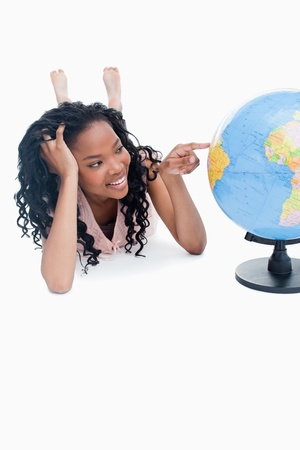 A young smiling girl is lying on the floor pointing at a globe against a white background photo