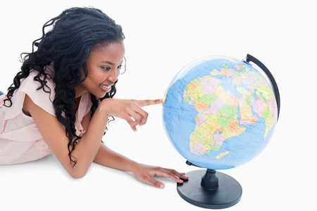 A young smiling girl is pointing at a globe against a white background Stock Photo - 13673387