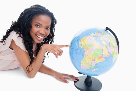 A young smiling girl is looking at the camera with her finger on a globe against a white background photo