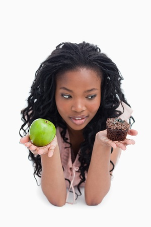 A young woman is choosing between an apple or a bun that she holds up on her palms photo