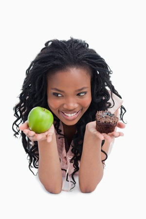 A smiling young woman is holding an apple and a bun on the palms of her hands against a white background photo