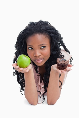 A thinking woman holding an apple and a bun on her palms against a white background photo