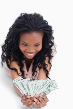 A young excited woman holding American dollars in her hands is smiling against a white background photo