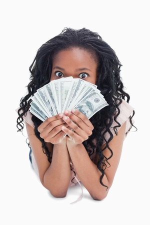 An excited woman is holding American dollars up to her face against a white background  Stock Photo - 13673136