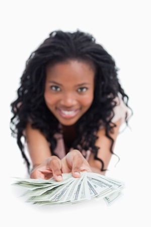 A smiling young woman is holding American dollars out in front of her against a white background Stock Photo - 13674135
