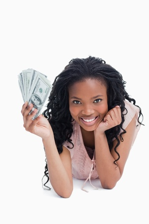 A young woman holding American dollars is resting her head on her hand against a white background photo