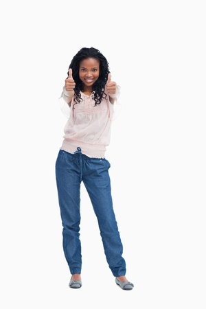 A young smiling woman is standing with her thumbs up against a white background Stock Photo - 13674895