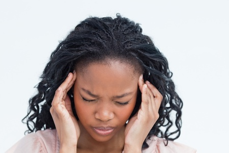 A woman with her hands up to the side of her head is having a headache photo
