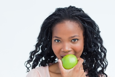 A head shot of a young woman who is eating a green apple photo