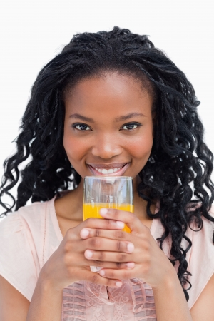A smiling young woman is holding a glass of orange juice with her both hands photo