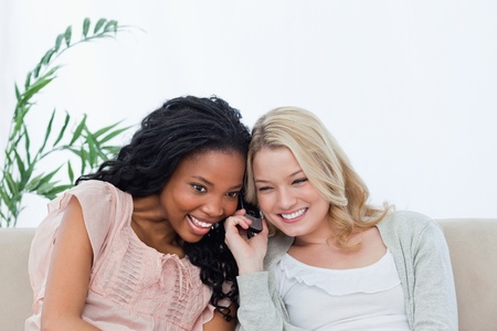 Two women listening together to a mobile phone Stock Photo - 13672428