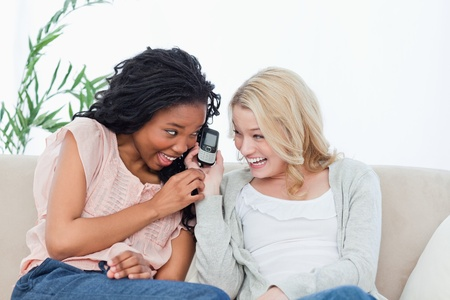 A laughing woman sitting on a couch is holding a mobile phone up to her friends ear Stock Photo - 13671074