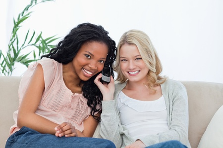 Two women are sitting down on the couch listening to a mobile phone and smiling at the camera photo