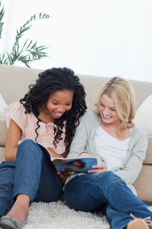 Two smiling women are sitting on the ground leaning against a couch reading a magazine Stock Photo - 13671265