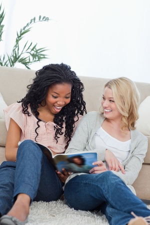 A surprised looking woman is reading a magazine with her friend photo