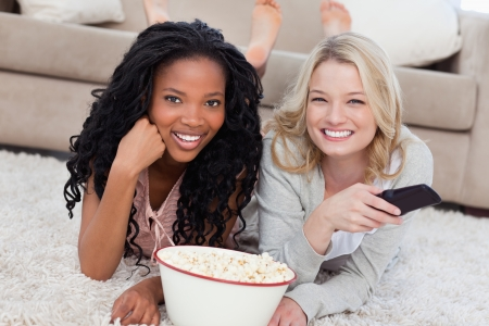 Two women lying on the ground with popcorn are smiling at the camera and have a TV remote photo