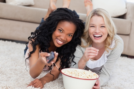 Two women lying on the ground with popcorn are smiling at the camera nd holding a TV remote photo