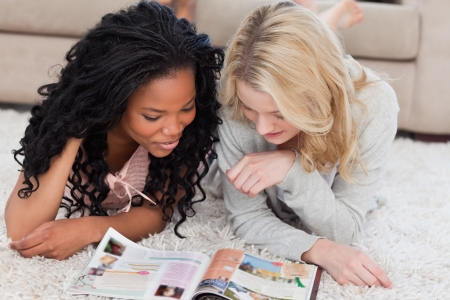 Two women are lying on the floor and reading a magazine Stock Photo - 13670538