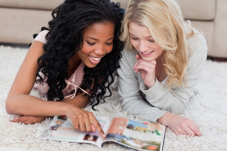 A woman lying on the floor is pointing at a magazine with her friend lying beside her photo