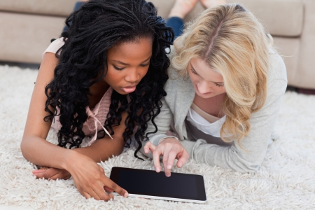 Two women are lying on the floor using a tablet Stock Photo - 13670345