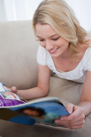 A smiling woman is lying down reading a magazine Stock Photo - 13668330