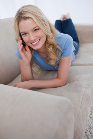 A young woman is lying on a couch and talking on her mobile phone Stock Photo - 13670891