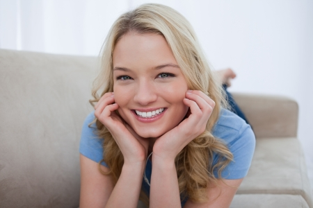 A young smiling woman is resting her head on her hands Stock Photo - 13671414