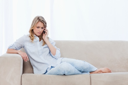 A woman who looks worried is lying on a couch talking on her mobile phone photo