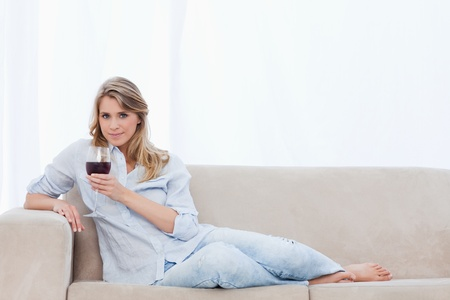 A woman lying on a couch holding a glass of red wine is looking at the camera Stock Photo - 13673152