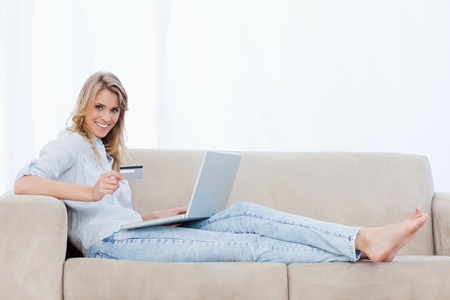 A woman holding a bank card is looking at the camera and lying on a couch with a laptop in front of her Stock Photo - 13673159