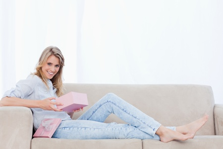 A smiling woman looking at the camera is lying on a couch holding a pink box photo