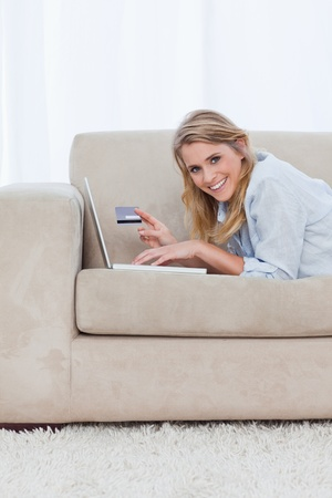 A woman resting on her elbows holding a bank card has a laptop and is looking at the camera Stock Photo - 13671380