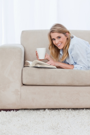 A smiling woman with a book is looking at the camera and holding a cup of coffee photo