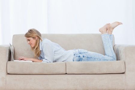 A side view shot of a woman who is lying on a couch with her legs held up using her laptop Stock Photo - 13671438