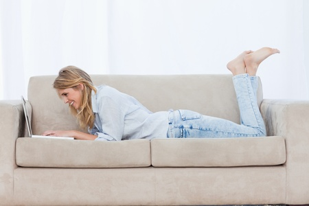 Side view shot of a smiling woman lying on a couch with her legs held up typing on her laptop Stock Photo - 13671357