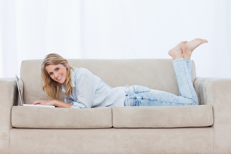 A smiling woman lying on a couch with her legs held up using a laptop Stock Photo - 13671377