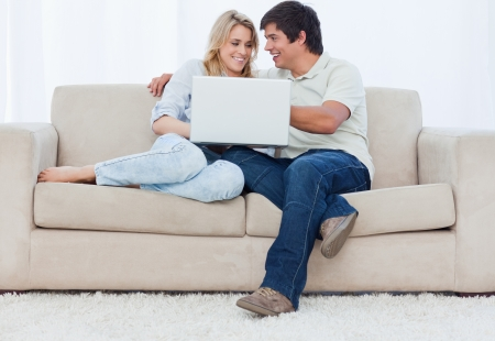 A young couple are sitting on a couch with a laptop photo