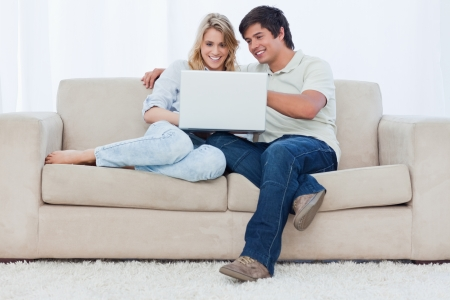 A smiling young couple are sitting together on a couch looking at a laptop photo