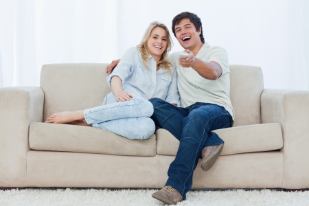 A young couple are sitting down on a couch looking at the camera and laughing photo