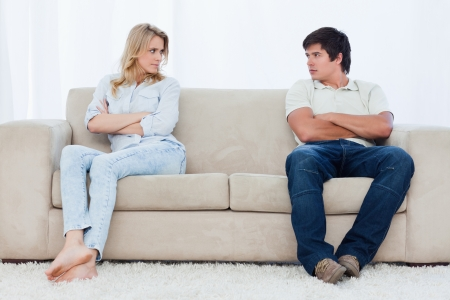 woman couch: A angry couple sit at the two ends of the couch with their arms folded looking at each other