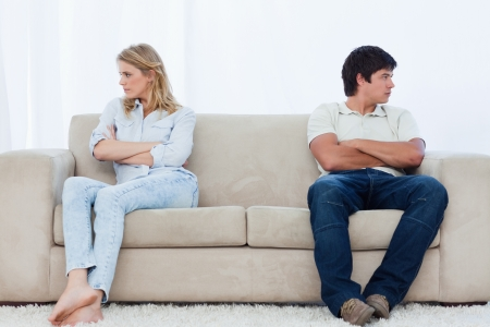 people fighting: A angry couple sit at the two ends of the couch with their arms folded looking away