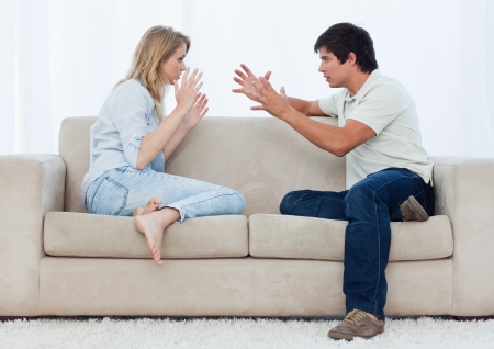 A young couple sitting on a couch are having an argument photo
