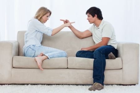 A couple sitting on a couch are looking at each other and pointing photo