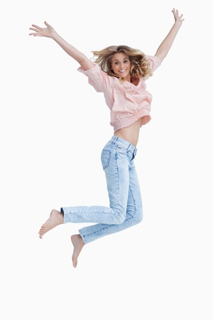 cheer full: A woman is jumping up in excitement with her arms raised against a white background