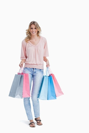 A full length shot of a woman who is carrying shopping bags against a white background photo