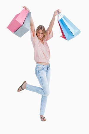 A woman is standing up holding shopping bags against a white background  photo