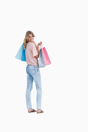 A rear view shot of a woman looking back at the camera who is carrying shopping bags against a white background photo